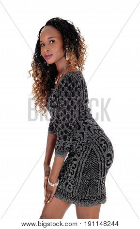 A gorgeous African American woman standing in profile in a short gray dress isolated for white background.