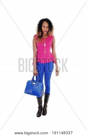 A lovely young African American woman standing in blue tights and a pink blouse with her blue purse isolated for white background.