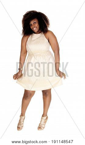 A smiling image of a African American women in a beige dress and messy hair standing isolated for white background.
