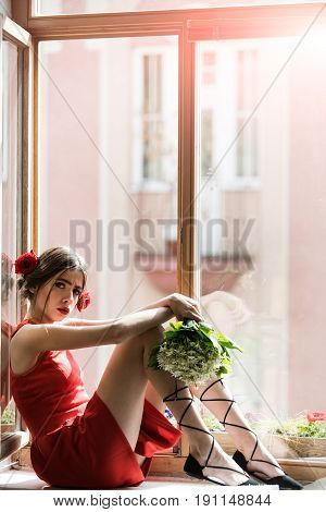 Woman In Red Dress In Orangery With Flower