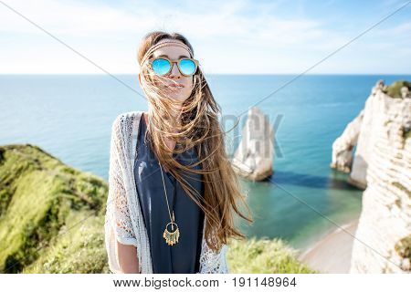 Lifestyle portrait of a young woman dressed in hippie style enjoying nature on the rocky coastline with great view on the ocean in France