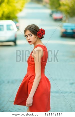 Pretty girl or cute woman young fashionable model in stylish red dress and roses in brunette hair or hairstyle walking outdoors on sunny day on road. Fashion. Summer vacation wanderlust