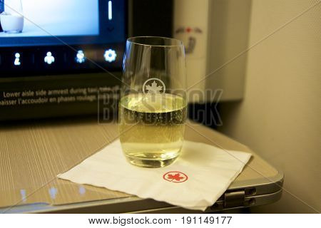 TORONTO, CANADA - JAN 28th, 2017: Air Canada Business class in a passenger plane. A glass of champagne on a folding table inside a Boeing 777-300ER from AC.