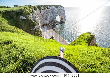 Landscape view on the famous rocky coastline with woman sitting on the precipice near Etretat town in France