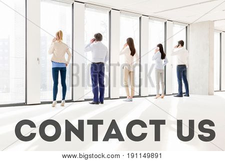 Full length rear view of business people using mobile phone in new office with the text saying contact us