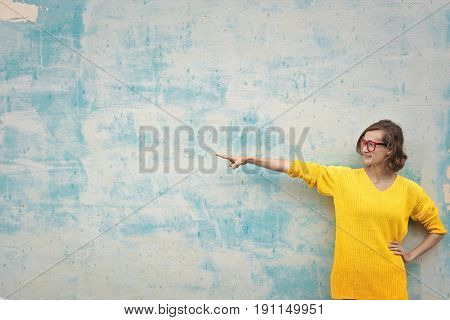 Nerd girl pointing indicating on the wall