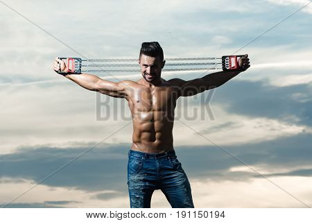 Man With Muscular Body Workout With Expander Gripper