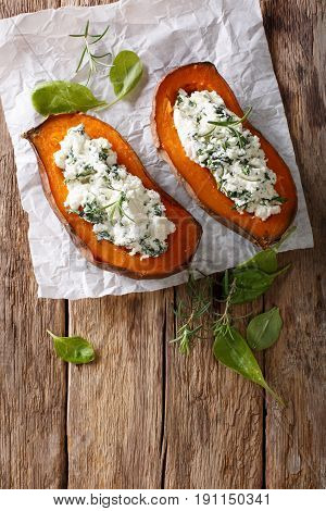 Baked Sweet Potato Stuffed With Spinach And Cream Cheese Close-up On The Table. Vertical Top View