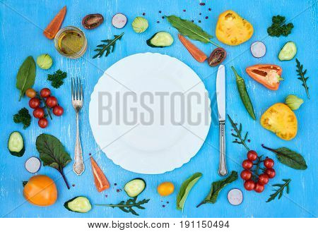 Colorfull fresh salad ingredients around empty white plate with silverware on light blue grunge background top view frame. Health salad making.