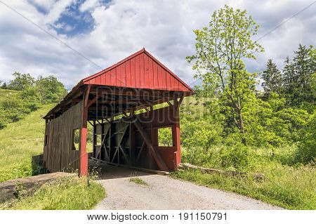 Built in 1887 the red Danley Covered Bridge crosses Robinson Fork a tributary of Wheeling Creek with cows grazing on hillsides near West Finley in rural Washington County Pennsylvania.