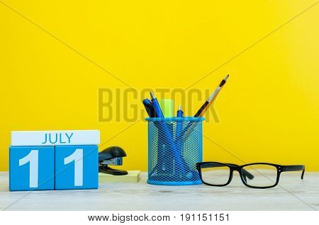 July 11th. Image of july 11, calendar on yellow background with office supplies. Summer time. With empty space for text.