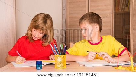 Cute children working on their homework together. Boy and girl doing homework at home.