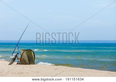Fishing Rod And Tent On Sea Shore