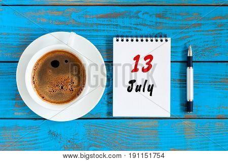 July 13th. Day 13 of month, calendar on blue wooden table background with morning coffee cup. Summer concept.