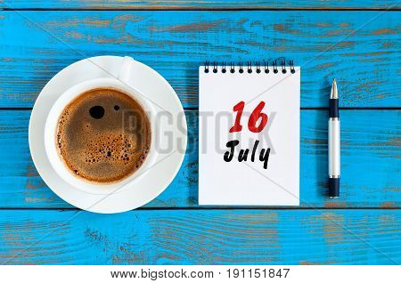 July 16th. Day 16 of month, calendar on blue wooden table background with morning coffee cup. Summer concept.