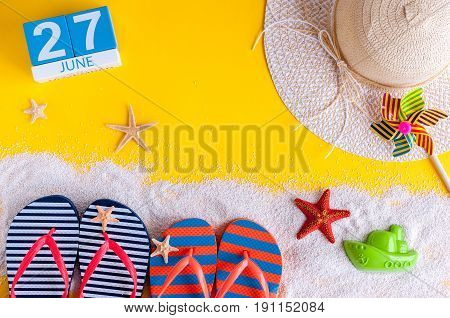 June 27th. Image of june 27 calendar on yellow sandy background with summer beach, traveler outfit and accessories. Summertime concept.