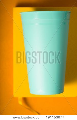 Blue plastic cup on the yellow background  top view vertical