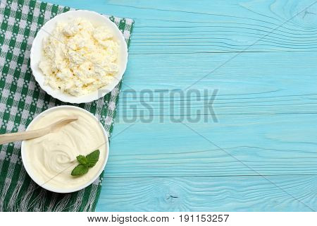 Milk background. Sour cream with cottage cheese on blue wooden background. Top view with copy space.
