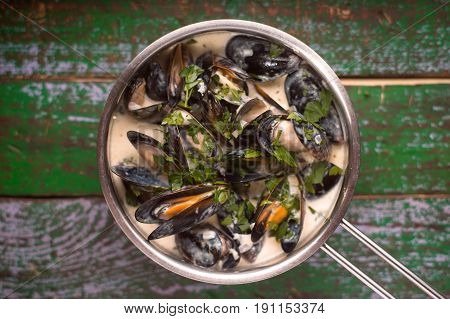 Mussels in Roquefort sauce on the old painted horizontal