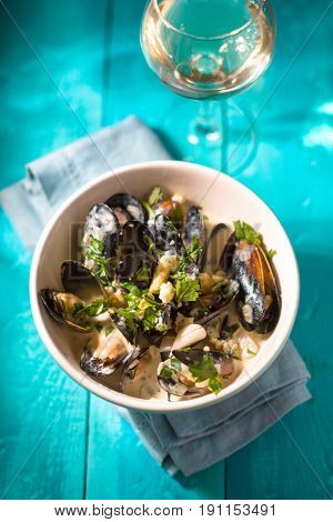 Mussels in Roquefort sauce  on the  wooden cyan background vertical