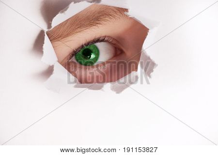 Spy eye looking through paper hole. little girl peeking through paper hole