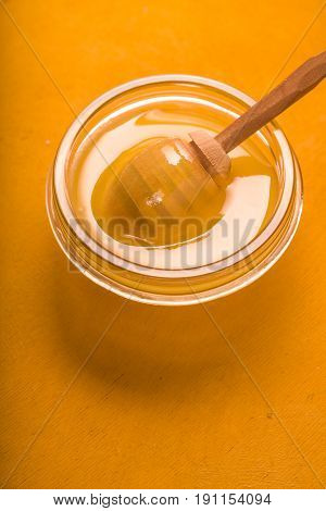 Honey on the glass bowl  with dipper on the yellow background vertical
