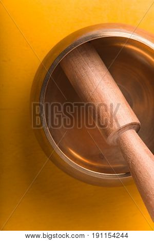 Tibetan singing bowl  on the yellow background top view vertical