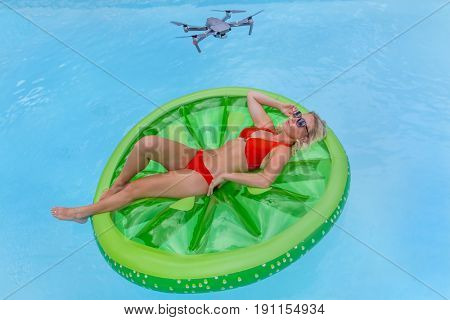 Blonde model posing in a water in an outdoor environment being photographed by a drone
