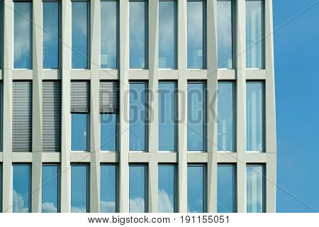 The facade of a high building with some windows closed