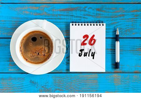 July 26th. Day 26 of month, calendar on blue wooden table background with morning coffee cup. Summer concept.
