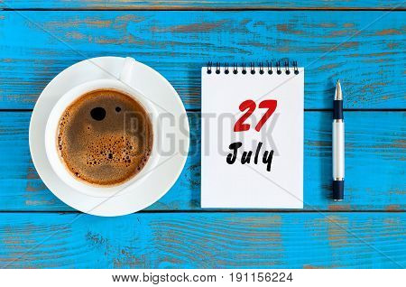 July 27th. Day 27 of month, calendar on blue wooden table background with morning coffee cup. Summer concept.