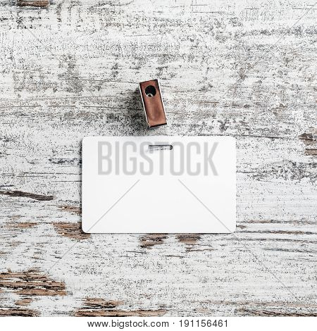 Blank white plastic badge. Template for ID. Badge on vintage wood table background. Mock up for branding identity. Top view.