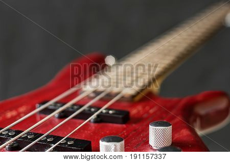 Close-up volume control of red bass guitar on gray background