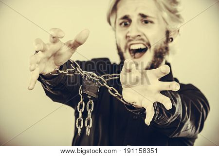 No freedom social problems human rights concept. Screaming furiously man with chained hands studio shot on light grey background