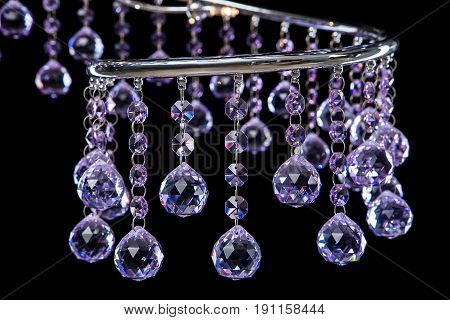 Modern high-tech chandelier of purple color crystals isolated on black. Chandelier for interior of the living room. Close-up