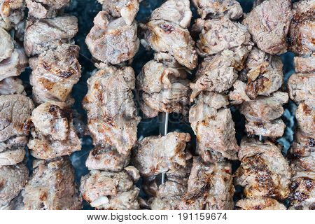 Texture of fried meat on skewers in a row as a background