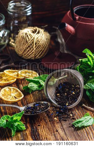 Dry Tea in Strainer and Spoon with Fresh Mint and Lemon Slices. Tangle with Two Jars and Teapot on Backdrop.