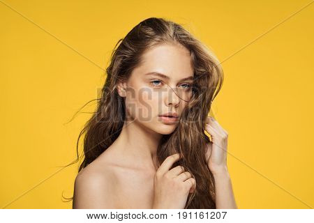 Woman with her hair on a yellow background.