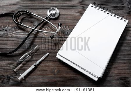 phonendoscope, syringe, ampoule and notebook on dark wooden desk top view make an appointment with doctor.