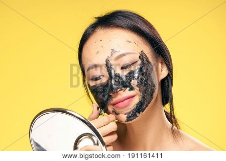 Woman takes off cosmetic mask, woman looks in mirror on yellow background.