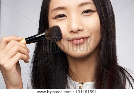 Woman with a cosmetic brush on a light background portrait.