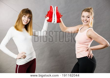 Two happy sporty smiling women presenting sportswear trainers red shoes comfortable footwear perfect for workout and training.