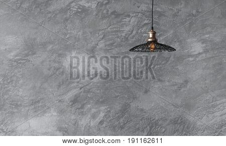 Pendant lamps in loft style against rough wall with gray cement plaster. Edison light bulbs.