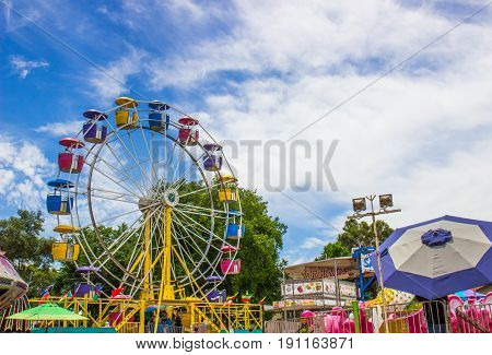 Ferris Wheel Against Blue Sky Background At Local County Fair