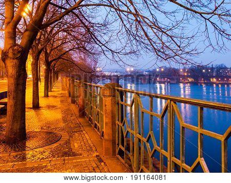Prague by night. Smetana embankment woth cobbled sidewalk, trees and metal ornamental railing, Czech Republic.