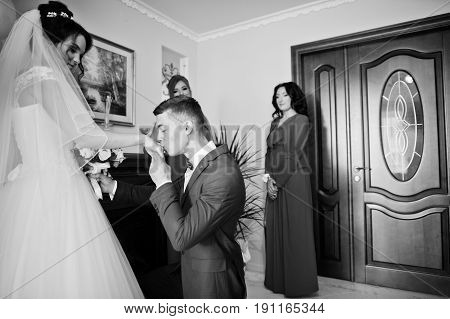 Groom Kneeling Down Kisses Hand Of A Bride And Gives Her A Beautiful Bouquet Of Roses. Black And Whi