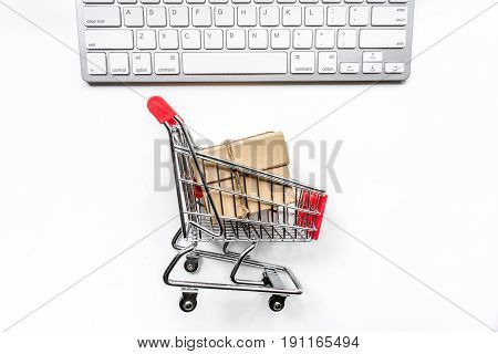 making purchase with keyboard and mini trolley on office desk background top view