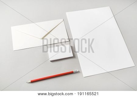 Photo of blank stationery set on paper background. Letterhead business cards envelope and pencil. Template for placing your design. Top view.