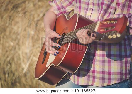 Female hands on acoustic guitar against hay roll background