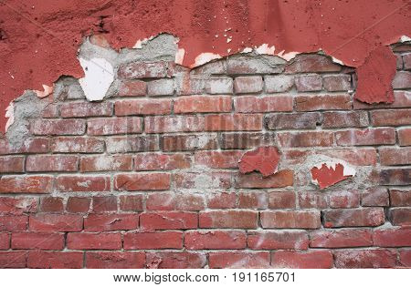 Brick wall built in the 1900s with peeling burgundy paint adding interest and texture.